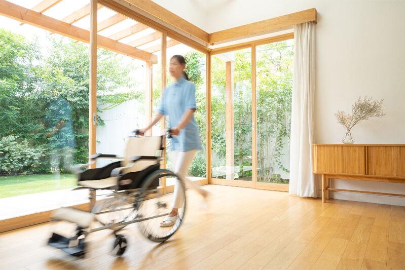 室内で車椅子を押す女性のイメージ