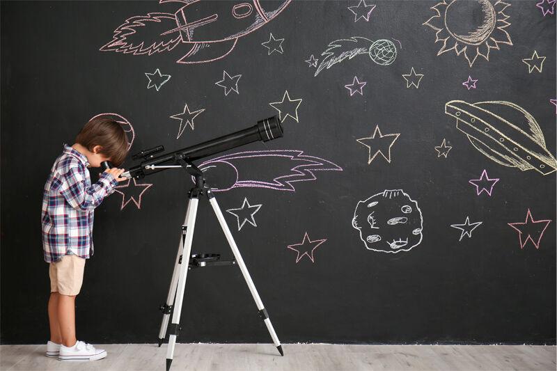 落書きされた壁の前で望遠鏡を覗く男の子