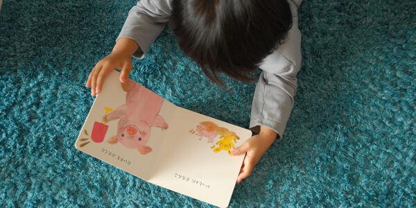 寝転がりながら絵本を読む幼児